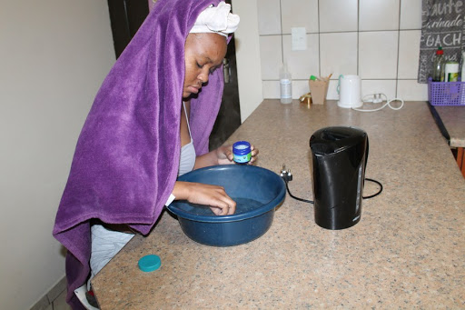 adds Vicks VapoRub to boiled water in order to make a warm moisture and use it for steaming in Windhoek, capital of Namibia, August 24, 2020. (Xinhua/Demetilie Amupolo)