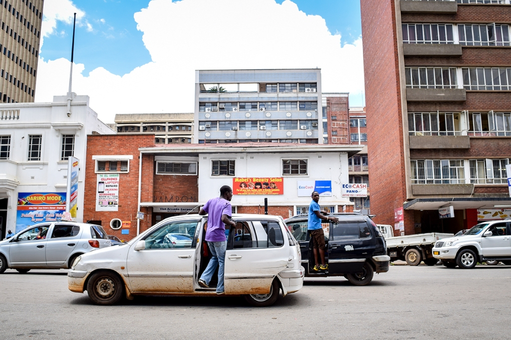 Pirate taxies illegally load people while stopped in the middle of the street in Harare, Zimbabwe.  (Linda Mujuru, GPJ Zimbabwe)